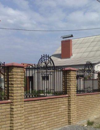 Темный кирпич с кованым забором