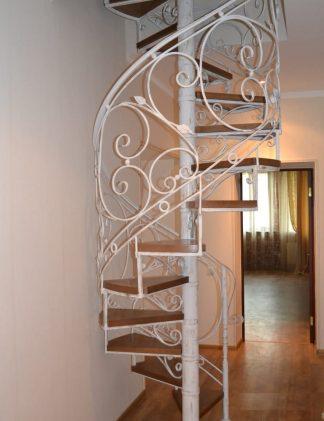 Белая винтовая лестница с коваными перилами
